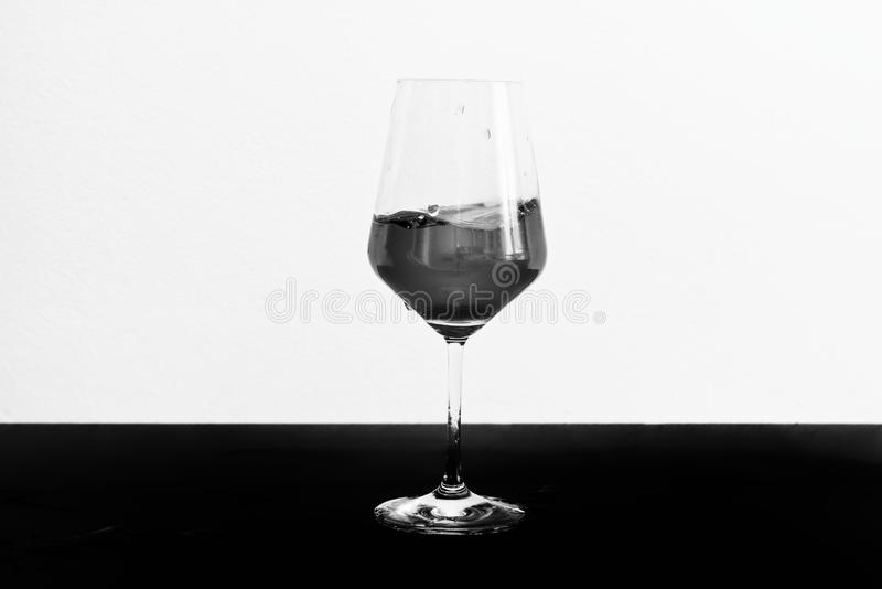 Black and white photo of red wine in motion in a glass stock image