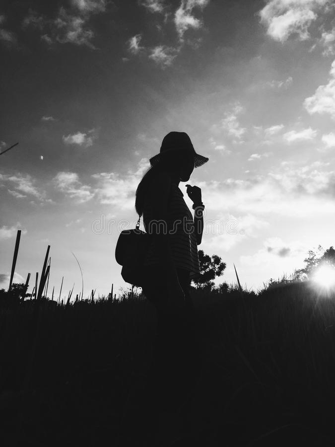 Black and white photo Silhouette of profile of woman in the hat in the nature stock image