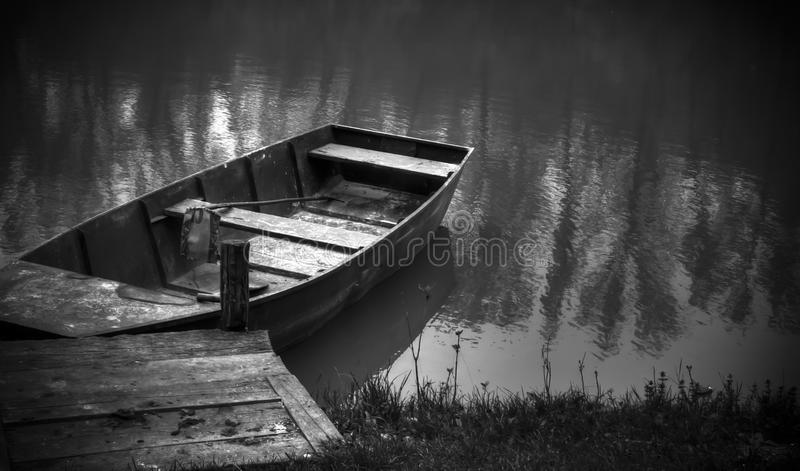 A small boat on a lake. A black and white photo of a small, old boat next to a small dock stock images