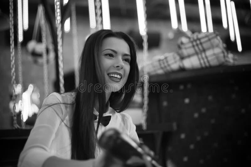 Black and white photo of smiling bartender girl. Black and white photo of beautiful cheerful brunette bartender girl serving alcohol drink at bar counter stock images