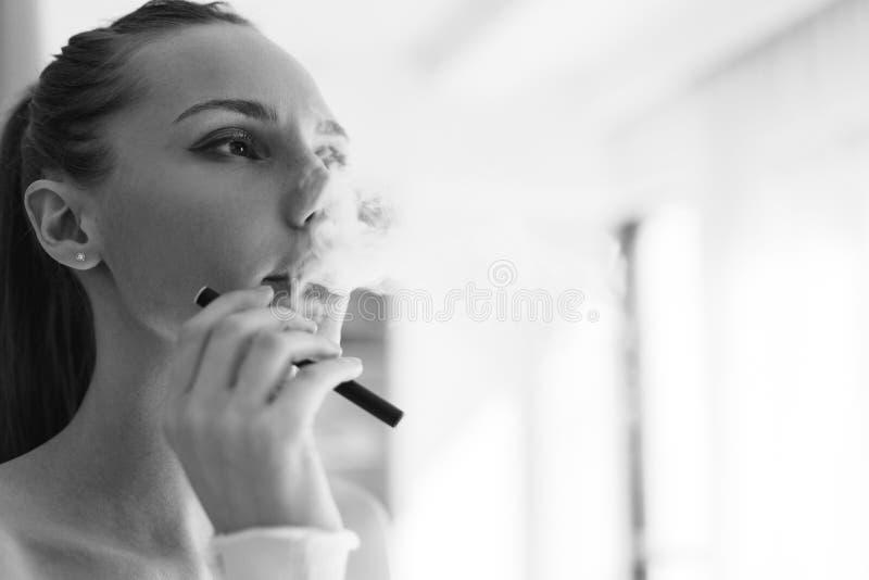Black-white photo of smoking girl stock photo