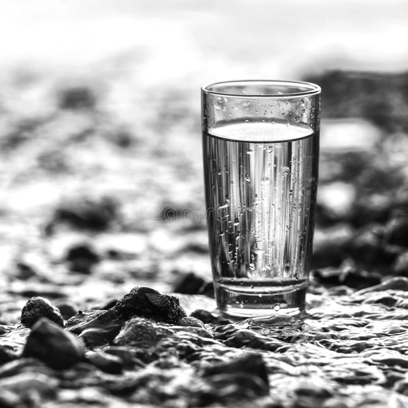 Black and white photo squared. A glass of water of water stands on the stones. Clean water stock photography
