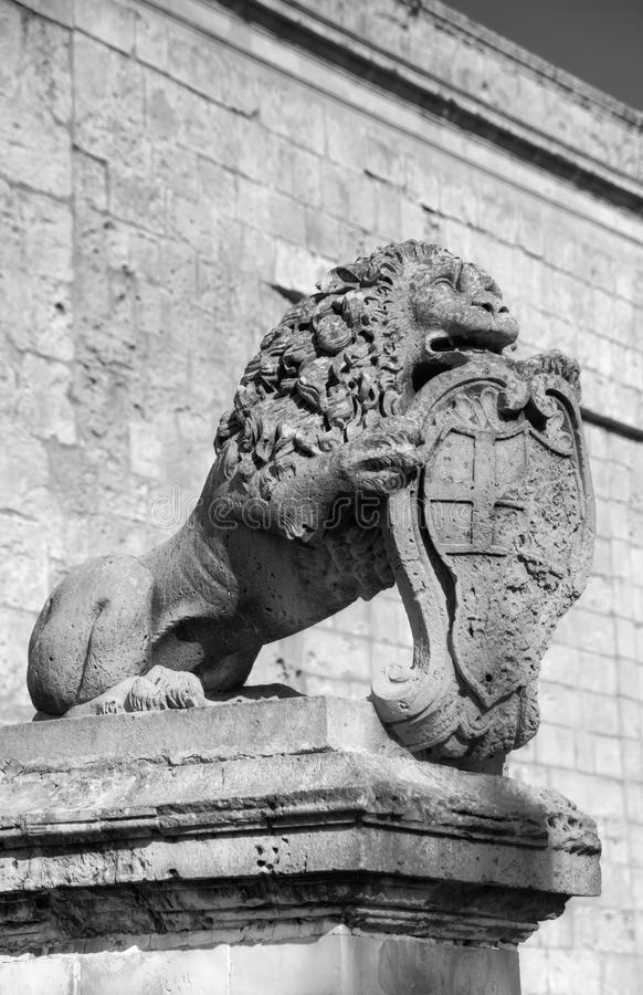 Black and white photo of a statue of a lion holding a historic crest in front of the Mdina gate, the historic Malta capital. Black and white photo of a statue of royalty free stock photography