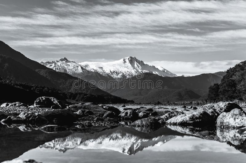 Black and white photo. Stunning landscpae of the reflection of the snow mountain on the river. Blue sky and some cloudy. I. Black and white photo. Stunning stock photos