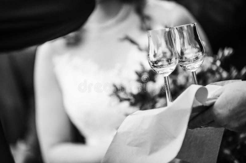 Two glasses on the stem, on the background bride and groom. Preparing for the first marital celebratory toast. Unrecognizable. Black and white photo of two stock image