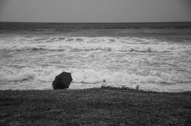 Black and white photo of an umbrella lying on the shore of a stormy sea royalty free stock photography
