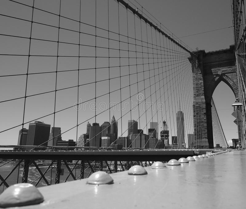 New York suspended on the Brooklyn Bridge. This black and white photo was taken on the Brooklyn Bridge and represents the skyline of Manhattan, New York. In the royalty free stock images