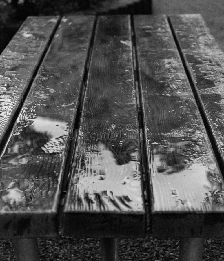 Black and white photo of wet wooden table royalty free stock photography