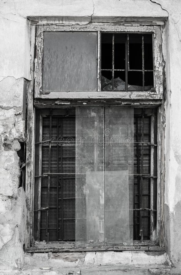 Black and white photo of an window frame with partially broken windows and metal bars inside the old dilapidated wall royalty free stock photography
