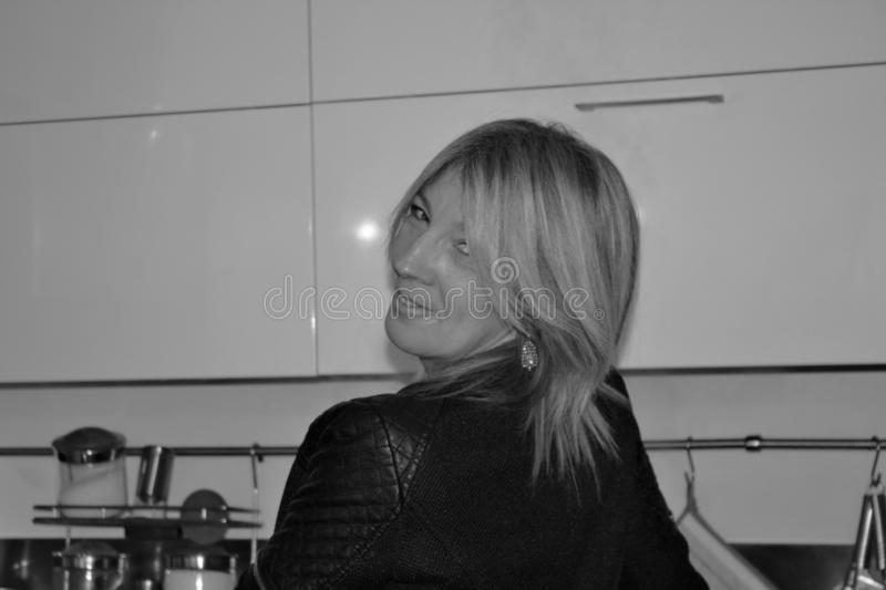Black and white photo of woman in the kitchen who turns with a smile after being called. Black and white photo of woman in the kitchen who turns with a smile stock photography