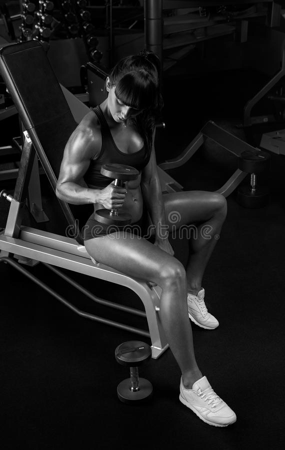 Black and white photo of woman lifting dumbbells sitting in the royalty free stock images