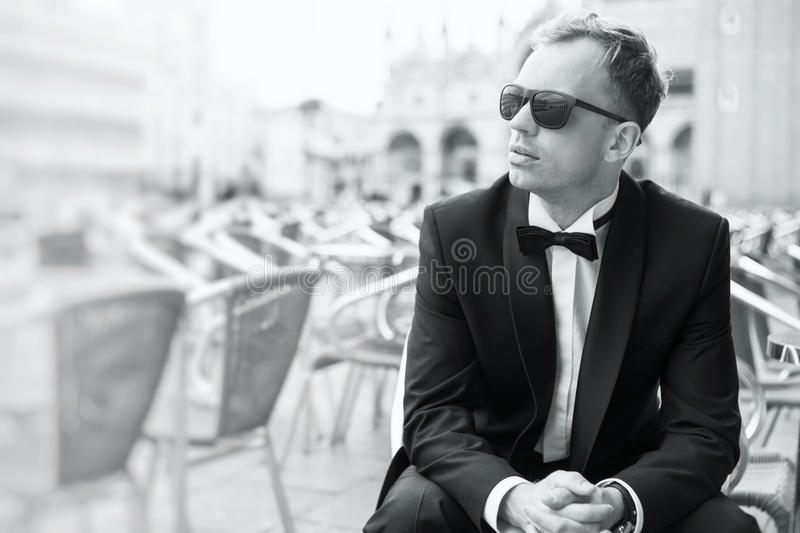 Black and white photo of young handsome man in tuxedo stock photography
