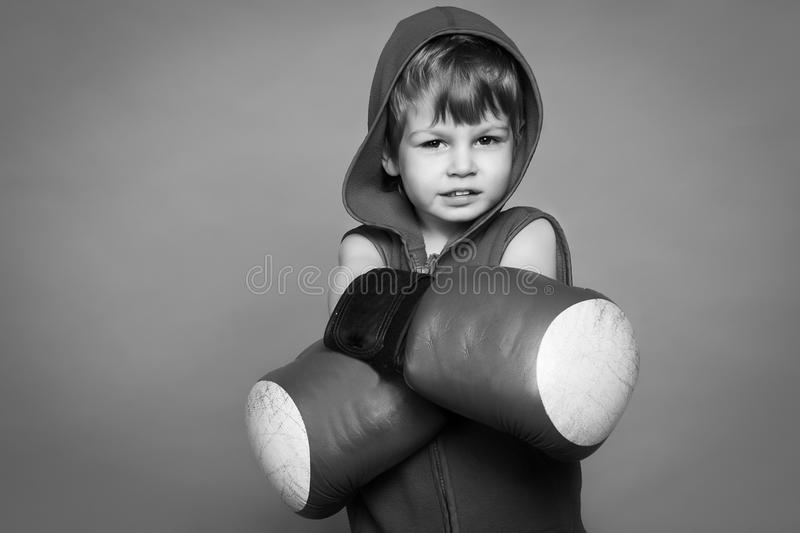 Black-and-white photograph of a boy with gloves and helmet. On the background stock photos