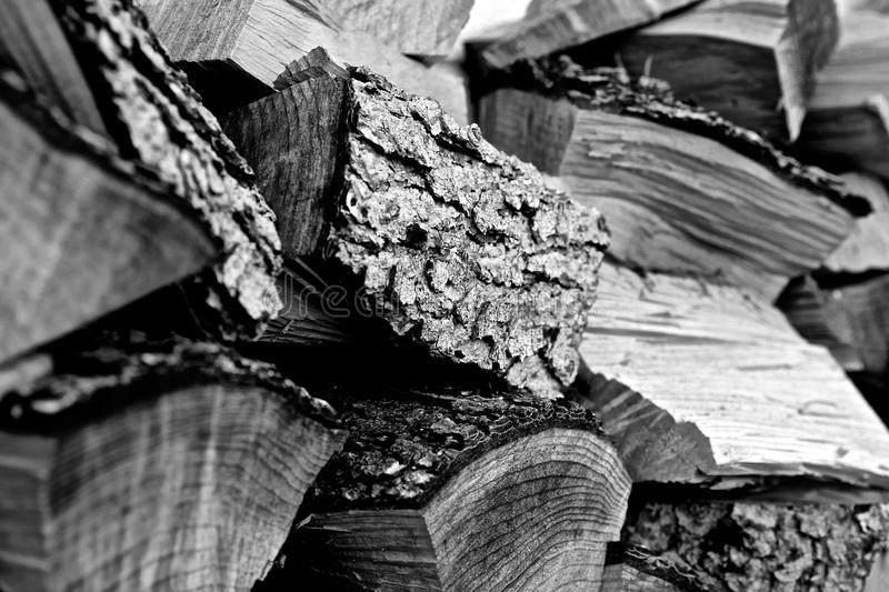 Black and white photograph of chopped and stacked firewood ready for winter fires in the fireplace. Closeup black and white photograph of chopped and stacked stock image