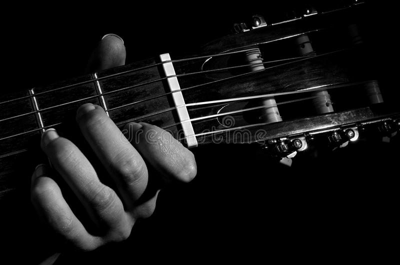 Hand guitar black background. Black-and-white photograph of hands of person who plays six-string guitar, the fingers are on the frets. The image is not colored stock images