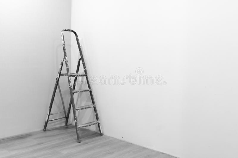 Black-and-white photograph of a ladder to repair a stained white paint standing in the corner of a freshly painted. royalty free stock image