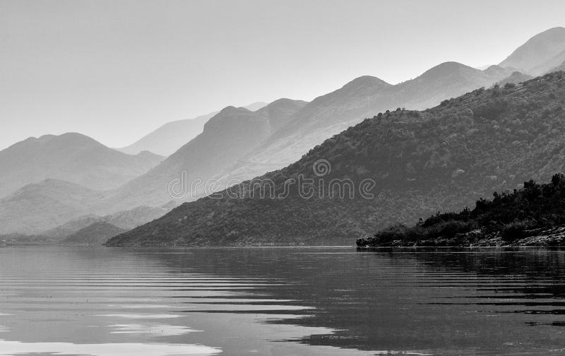 Calm and peaceful atmosphere on the lake Skadar in Montenegro. Black&white photograph of the lake Skadar in Montenegro with hills behind. On the water small royalty free stock photos