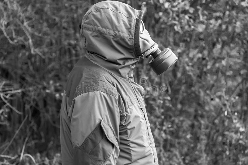 Black and white photograph of a man standing in a gas mask. A blurred background royalty free stock photo