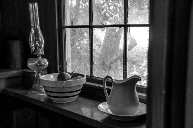 Simpler Times. Black and white photograph with natural light through a vintage window of an old home  that  brightens the simple forms on a shelf of a lantern royalty free stock image