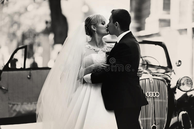 Black and white photograph of a wedding couple kissing behind a. Retro car stock photography