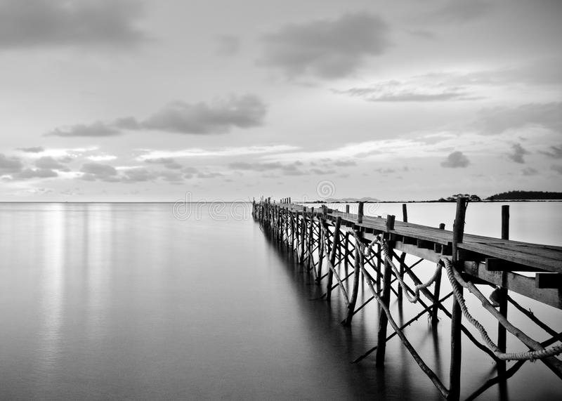 Black and white photography of a beach wooden pier stock image