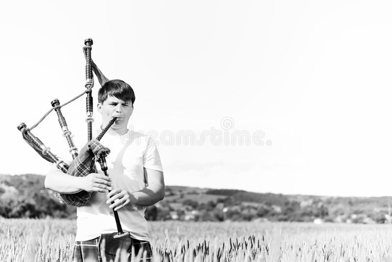 Black white photography of man enjoying playing pipes in Scottish traditional kilt on green outdoors copy space summer royalty free stock photography