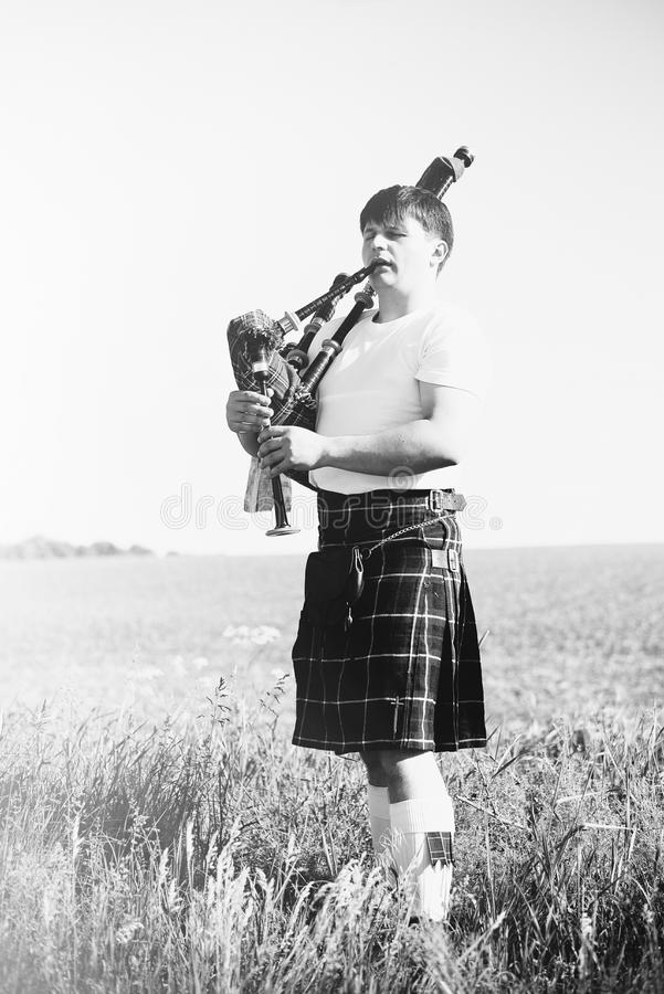 Black white photography of man enjoying playing pipes in Scottish traditional kilt on outdoors copy space summer field stock photos