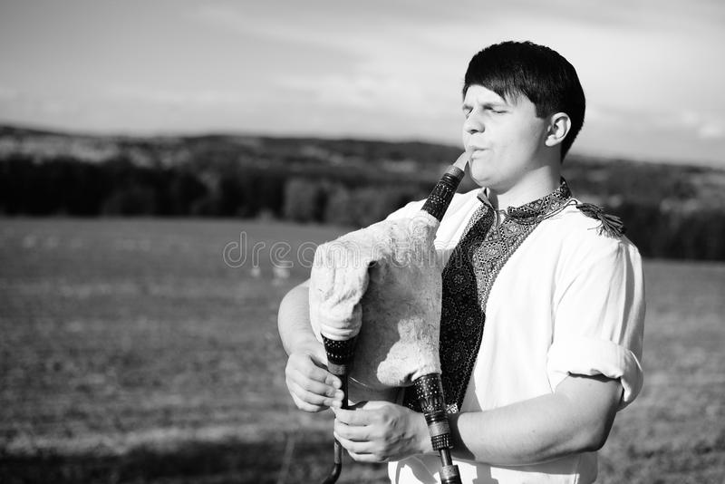 Black and white photography of man enjoying playing pipes in Ukrainian traditional shirt on outdoors summer field stock photos