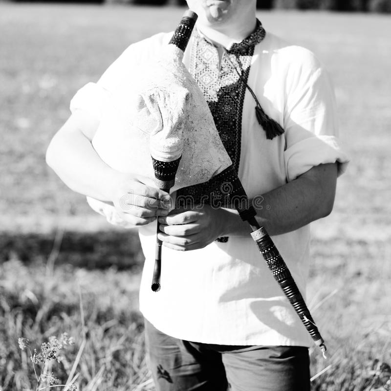 Black and white photography of man enjoying playing pipes in Ukrainian traditional shirt on outdoors summer field royalty free stock images