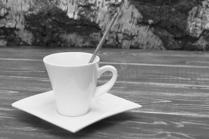 Exclusive porcelain white coffee pair of the original form with metal spoon on dark wooden tabletop against the background of stock image