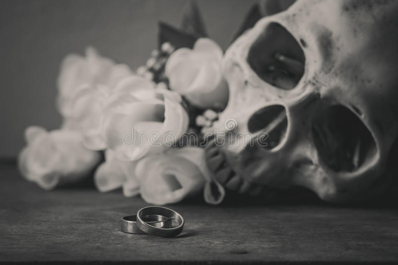Download black and white photography with rings human skull and roses on stock image