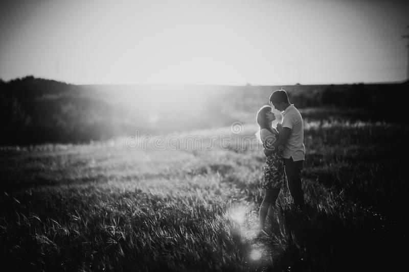 Black white photography romantic couple standing and kissing on background summer field. Black white photography romantic couple standing and kissing on royalty free stock images
