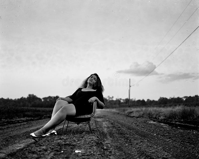 Black and White Photography of Woman on Chair on Road royalty free stock photos