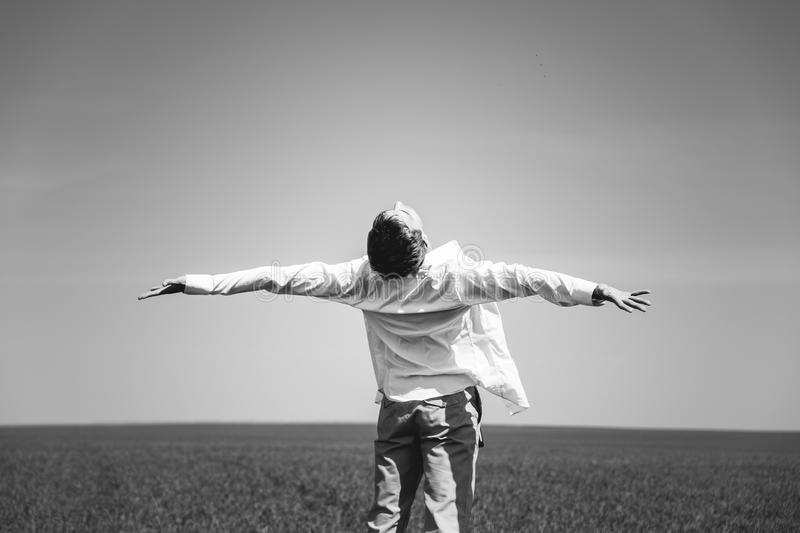 Black and white photos. A young guy. Is standing in the field with arms outstretched, his back to the camera royalty free stock photography