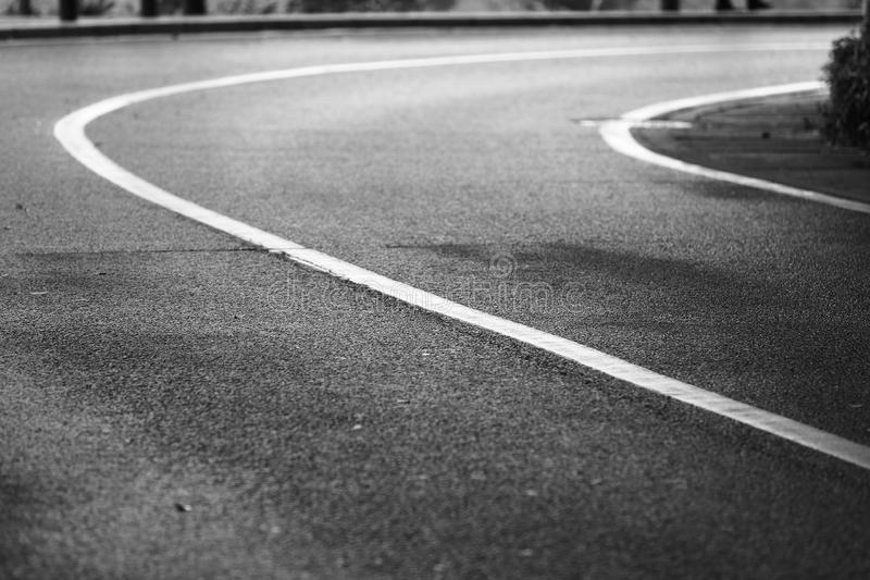 Black and white picture of an empty nature road,turn right royalty free stock photos
