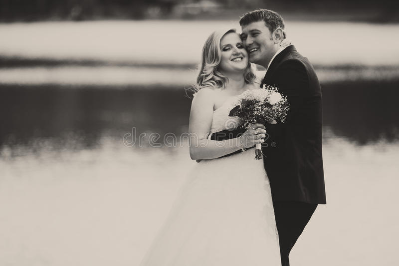 A black and white picture of a happy wedding couple standing behind a lake royalty free stock photo