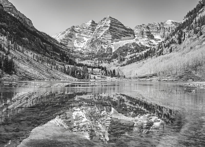 Black and white picture of Maroon Bells reflected in lake. stock photography