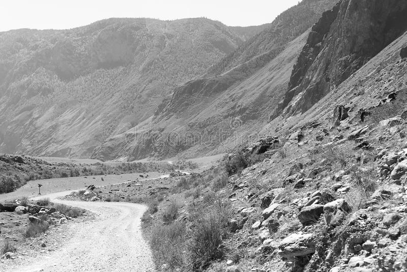 Black and white photograph of the Altay mountain road, a road without asphalt, wild Altai, Altai Republic, Russia royalty free stock image