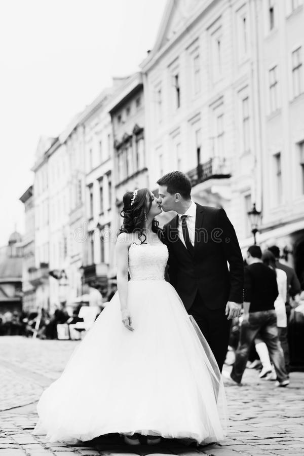 Black and white picture of newlyweds kissing on the old city square.  stock photos