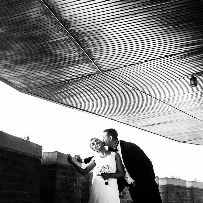 Black and white picture of newlyweds kissing tenderly on the balcony.  stock photography