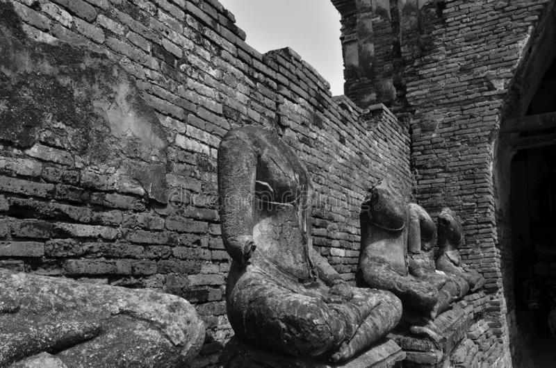 Row of headless Buddha images beside broken brick wall. Black and white picture of row of headless Buddha images beside broken brick wall stock image