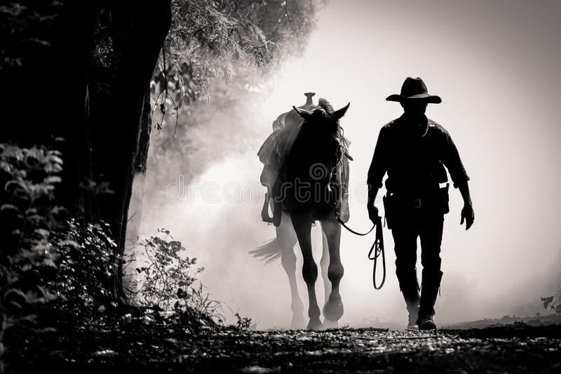 Black and white picture silhouette of cowboy and the horse in the morning sunrise stock photos