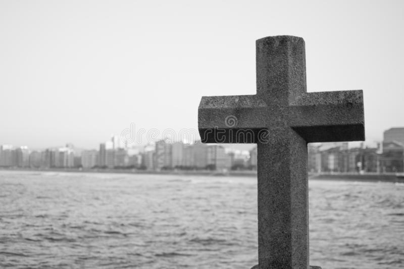 Black and white picture of a stone cross with the sea and buildings at the background in San Lorenzo beach, Gijon, Asturias, Spain.  royalty free stock images