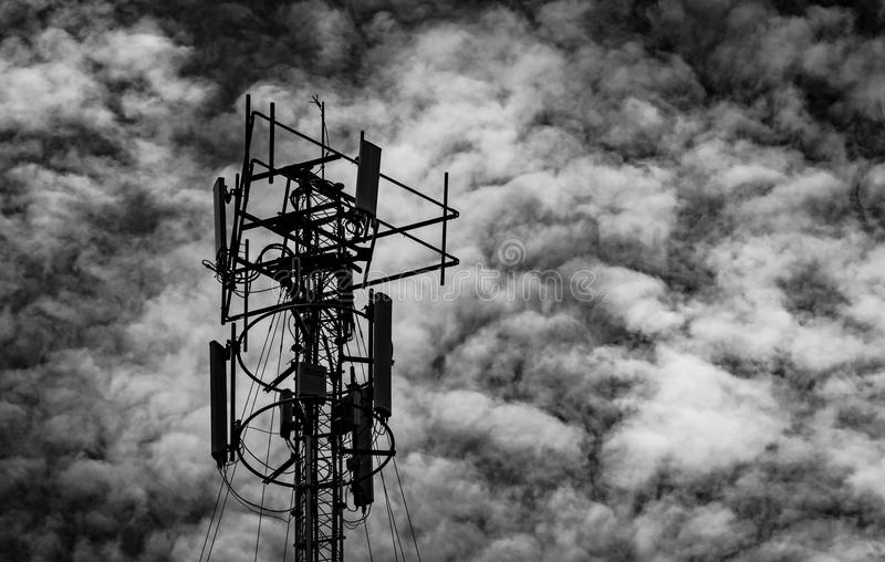 Black and white picture of telecommunication tower against grey sky and white clouds. Antenna on dark sky background. Radio. And satellite pole. Communication royalty free stock photography