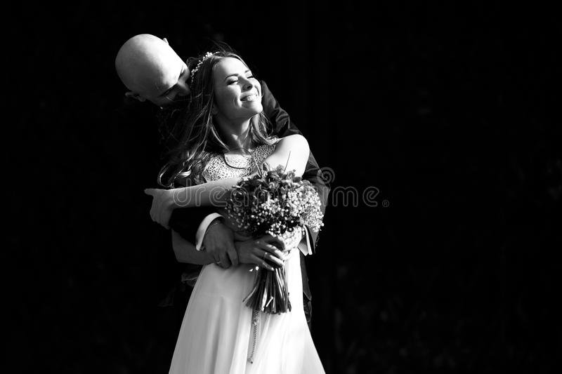 A black and white picture of a wedding couple hugging and enjoying the sun stock photo