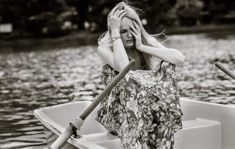 Sad drepressed woman sitting alone on a row boat. royalty free stock images
