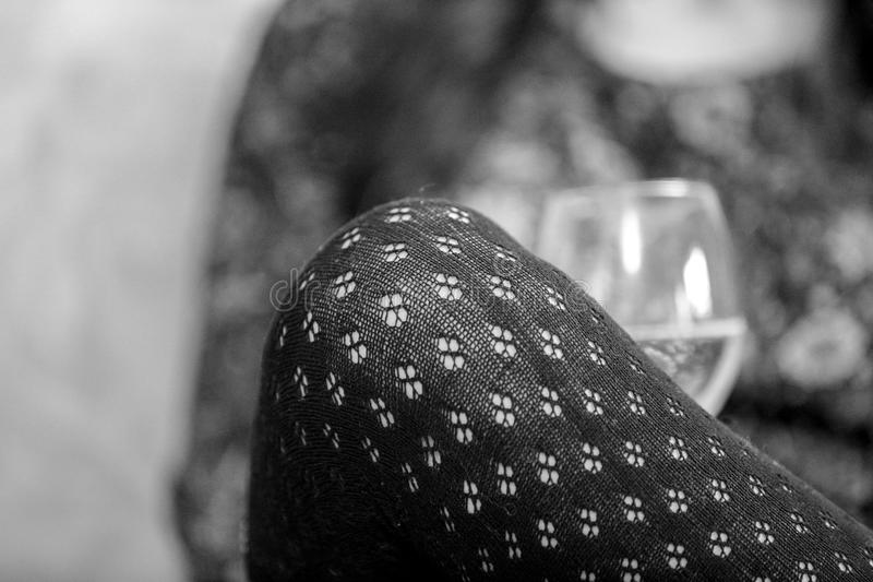 Black and white picture of a woman`s knee in tights stock photos