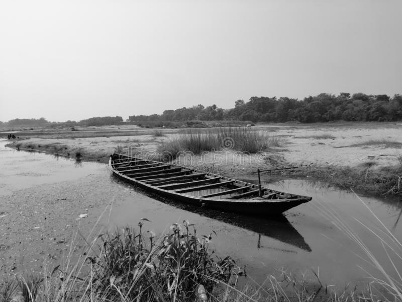 A black and white picture of a wooden boat damped on the river side stock images