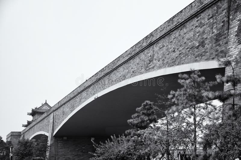 Black and white Xian City Wall. A black and white picture of the xian city wall bridge over trees and road in Shaanxi Province China royalty free stock images