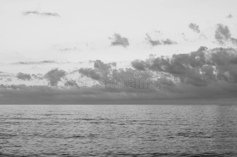 Black and white picturesque cloudy sky seascape. Picturesque cloudy sky seascape. High heaven with fluffy clouds. Gorgeous cloudscape above calm mirrored sea royalty free stock images